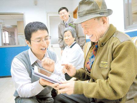 新莊日照中心的86歲阿公王清河(右),玩iPad玩得笑呵呵。