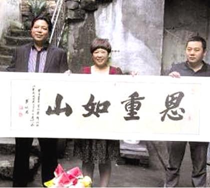 富豪何榮鋒(左)送恩人戴杏芬(中)「恩重如山」牌匾。p1026-a4-07