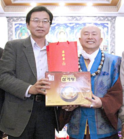 圖為盧師尊與貴賓洪國浩鎮長(左二)在派送獨居長者人蔘雞及祈願福袋捐贈儀式上合影p1044-01-02a
