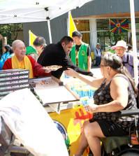 圖為溫哥華華光功德會總裁蓮慈金剛上師(左2)和名披薩連鎖店Freshslice溫哥華全球總部副總裁Jame先生(左1)在日本公園派發披薩給遊民p1071-10-01