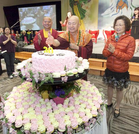 圖為師尊搧西雅圖雷藏寺30周年廟慶蛋糕上蠟燭燭火,右為師母,左為德輝上師p1074-08-05