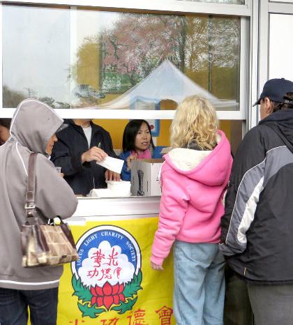 圖為遊民排隊領取華光功德會派發的熱食餐盒p1076-13-01B