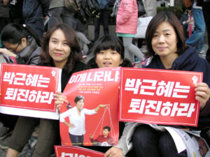 南韓民眾對總統朴槿惠閨密崔順實干政深感不滿,1對來自大田市的母女手舉字牌寫著「朴槿惠退陣」。p1133-a4-01