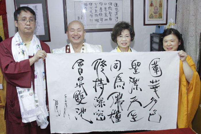 圖左起蓮聖同修會呂艾杰助教、師尊、師母與堂主鄭師姐手拿墨寶合影p1156-11-04