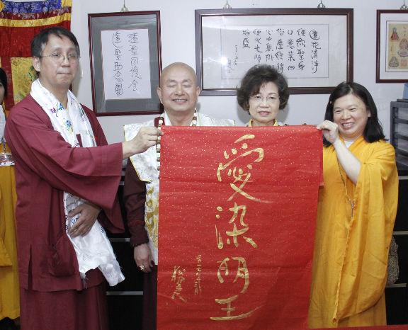 圖左起蓮聖同修會呂艾杰助教、師尊、師母與堂主鄭師姐手拿墨寶合影p1156-12-02