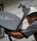 Justin Preziosi, field service specialist for Dish Network Corp., installs a satellite television system at a residence in Denver, Colorado, U.S., on Tuesday, Aug. 6, 2013. Dish Network Corp., the third-largest U.S. pay-TV company by customers, and Charter Communications Inc., the eighth-biggest, both may look to combine with competitors as a way to gain leverage in negotiations with TV networks to carry their programming. Photographer: Matthew Staver/Bloomberg via Getty Images