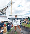 People hold up signs in support of asylum seekers during a rally outside the Olympic Stadium in Montreal, Sunday, August 6, 2017. The stadium is now being used as a temporary shelter for some of the hundreds of asylum claimants pouring across the New York-Quebec border every day. THE CANADIAN PRESS/Graham Hughes